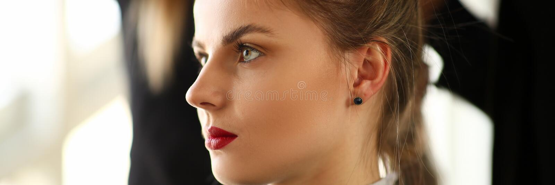 Klient f?r ung kvinna som f?r frisyr i sk?nhetsalong royaltyfri fotografi
