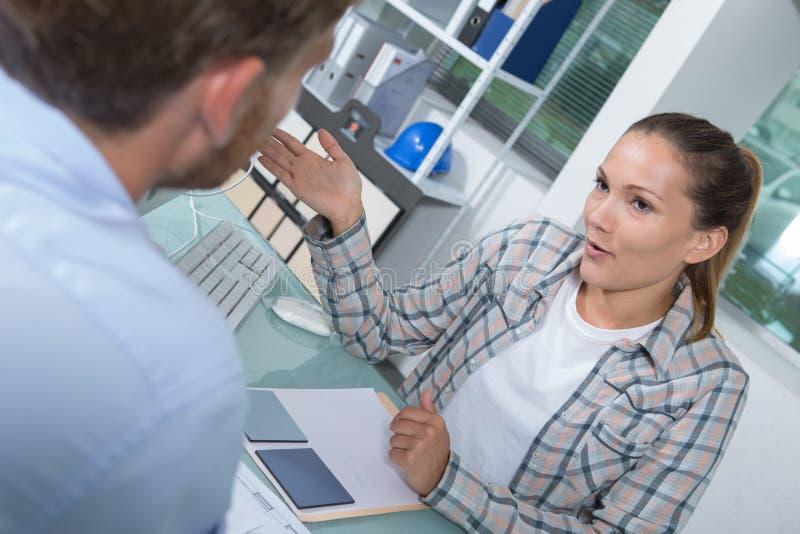 Klient i ?e?ski pieni??ny agent w dyskusji przy biurkiem fotografia stock