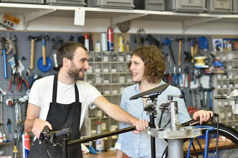 Klient i handlowiec w bicyklu sklepie - nabywa i naprawa bic fotografia stock