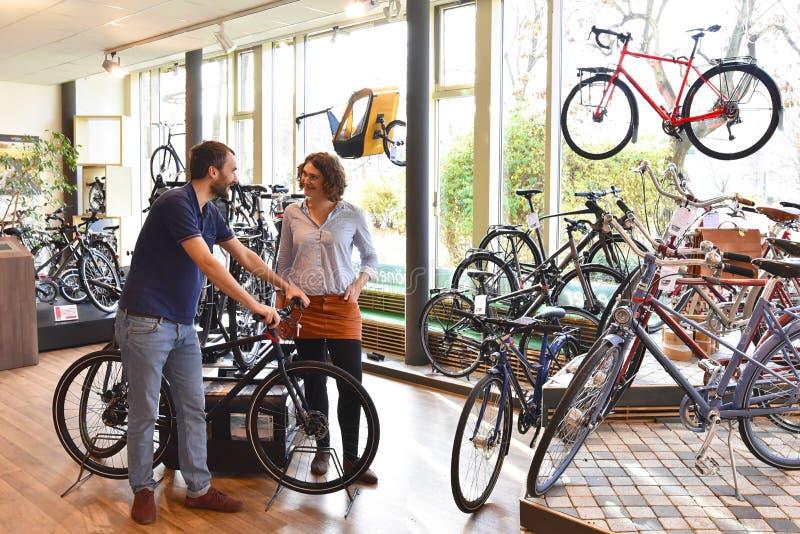 Klient i handlowiec w bicyklu sklepie obsługa klienta - nabywa i naprawa bicykle - obraz royalty free