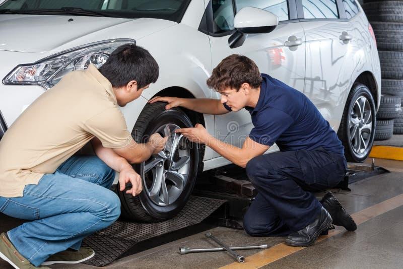 Klient I mechanik Dyskutuje Nad Samochodową oponą fotografia royalty free