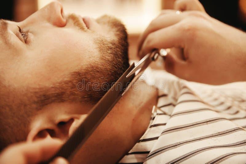 Klient jest męskim modnisia czułością dla brody w zakładzie fryzjerskim Ogolenie włosy fotografia royalty free