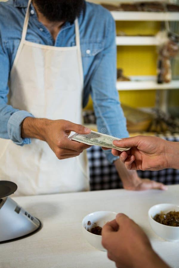 Klient płaci rachunek gotówką przy mięsnym kontuarem zdjęcie royalty free