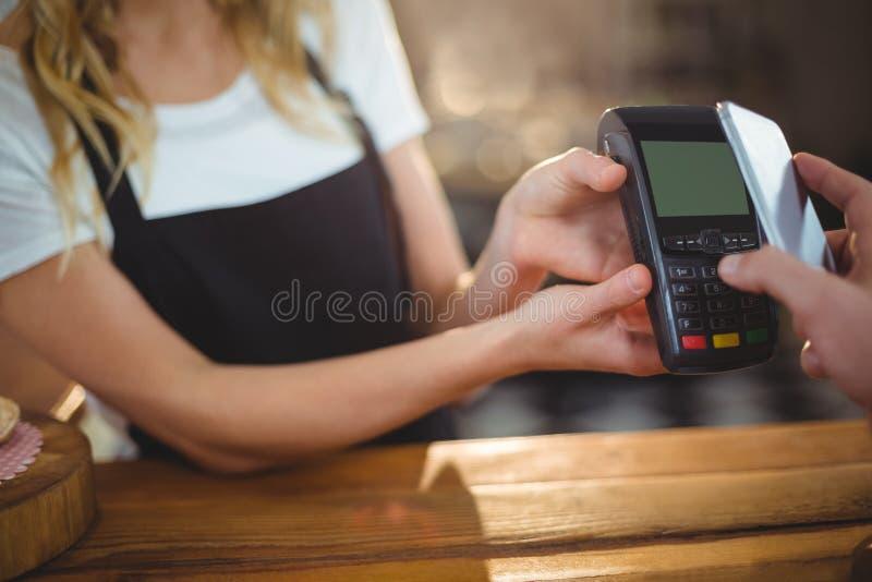 Klient płaci rachunek przez smartphone używać NFC technologię obraz royalty free