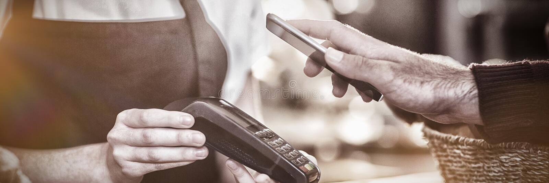Klient płaci rachunek przez smartphone używać NFC technologię w kawiarni zdjęcie stock