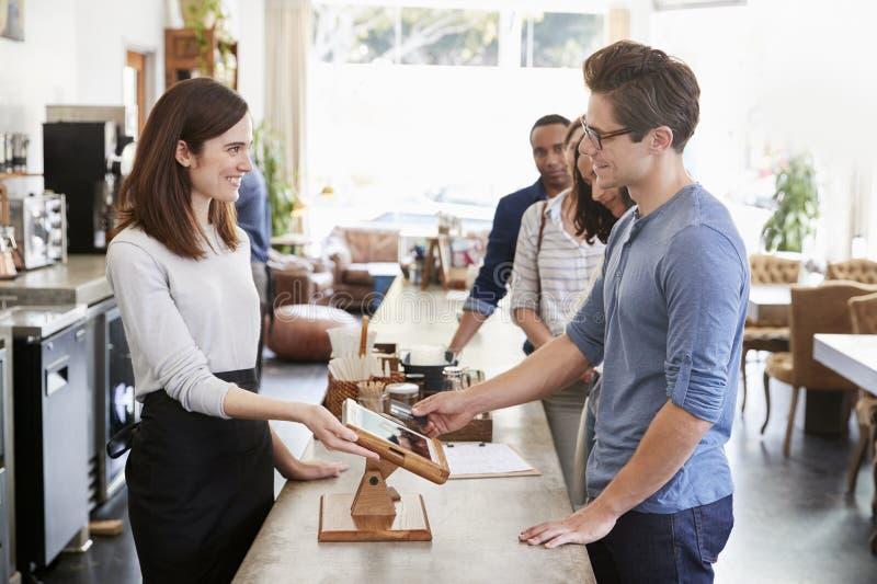 Klient przy przodem kolejka płaci w sklep z kawą zdjęcia stock