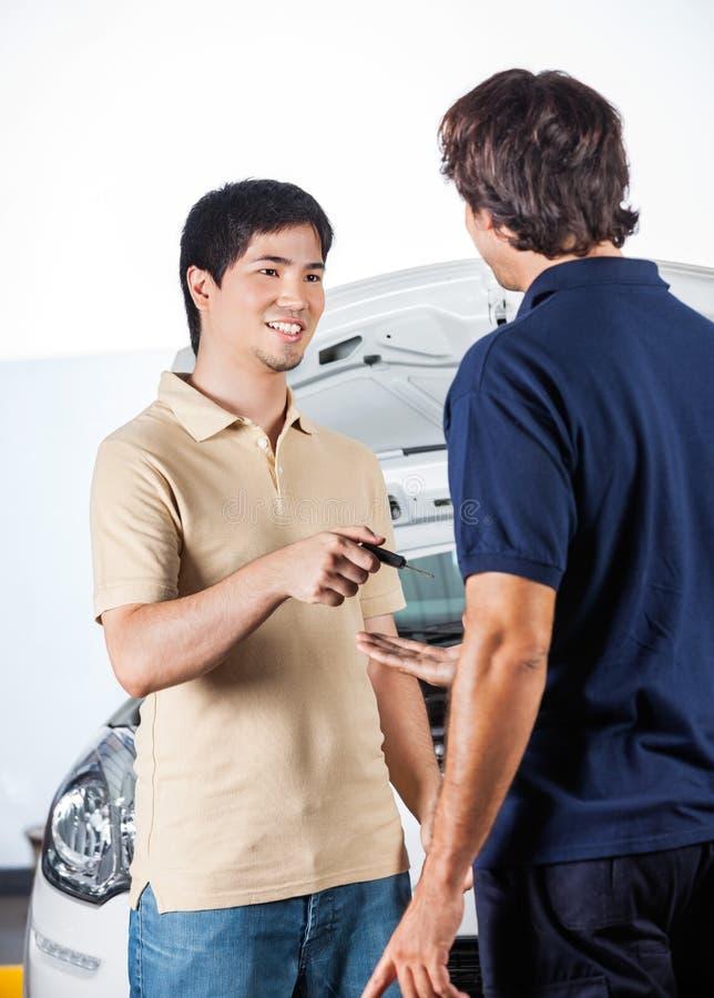 Klient som ger biltangenter till mekanikern At Repair Shop arkivfoto
