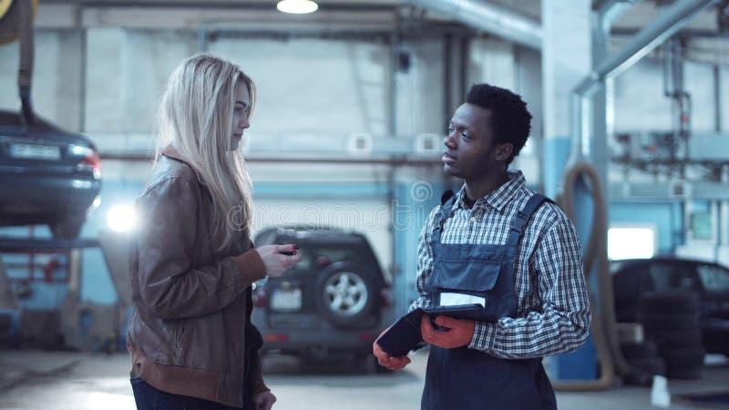 Klient som ger tangenter från bilen till mekanikern royaltyfri bild