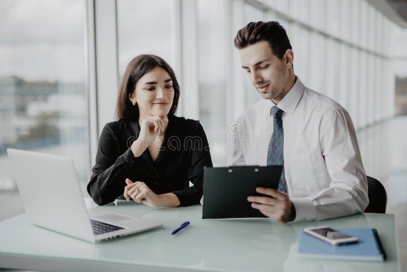 Klient som undertecknar ett dokument i ett kontor med en affärskvinna som ser avtalet kontorsarbete royaltyfri foto