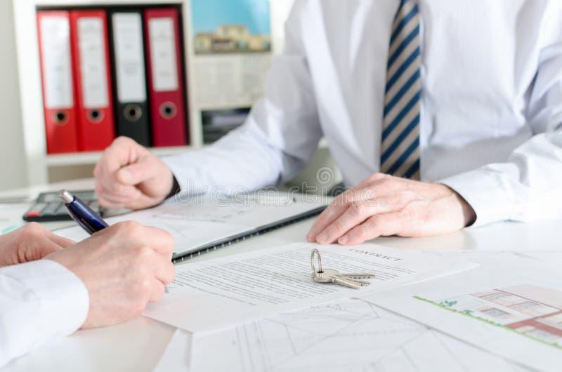 Klient som undertecknar ett fastighetavtal arkivbild