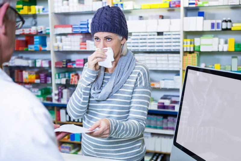 Klienta kichnięcie podczas gdy dawać recepcie farmaceuta fotografia royalty free