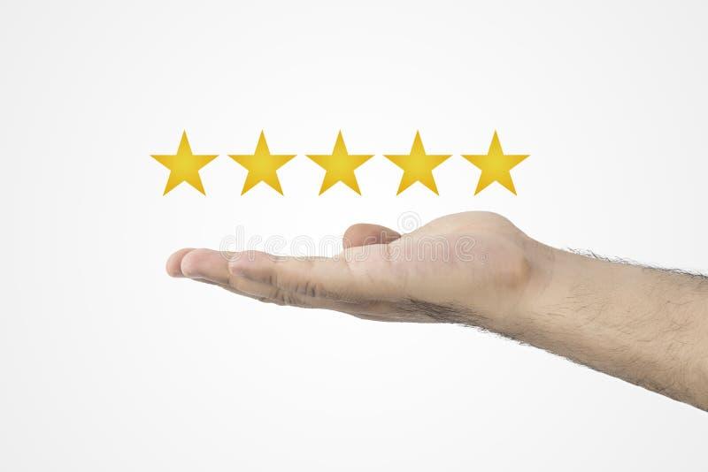 Klienta przeglądowy pojęcie Ratingowe złote gwiazdy Informacje zwrotne, reputaci i ilości pojęcie, Ręka trzyma złoci pięć gwiazdo obraz stock