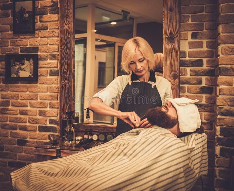 Klienten i en barberare shoppar arkivfoto