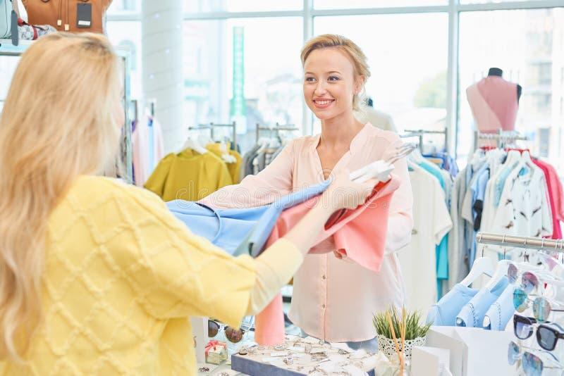 Klienten och säljaren i klädlager royaltyfri fotografi
