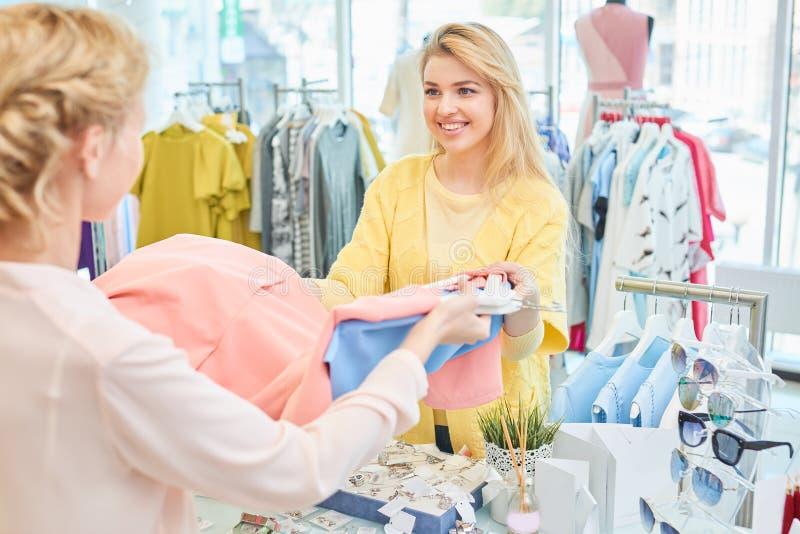 Klienten och säljaren i klädlager royaltyfri foto