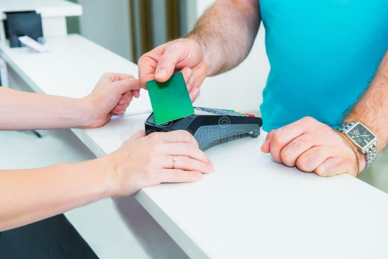 Klienten på mottagandeskrivbordet som gör contactless betalning med nfcteknologikreditkorten på, shoppar, kliniken, hotellservice arkivbild