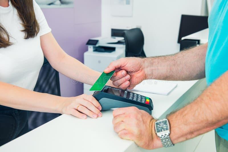 Klienten på mottagandeskrivbordet som gör contactless betalning med nfcteknologikreditkorten på, shoppar, kliniken, hotellservice royaltyfria foton