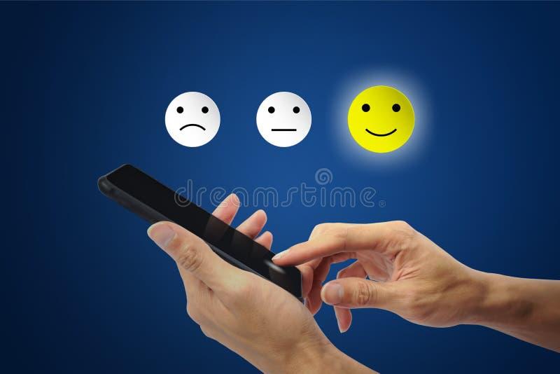 Klienten som anv?nder handen, v?ljer den lyckliga framsidaleendesymbolen p? smartphonen royaltyfria bilder