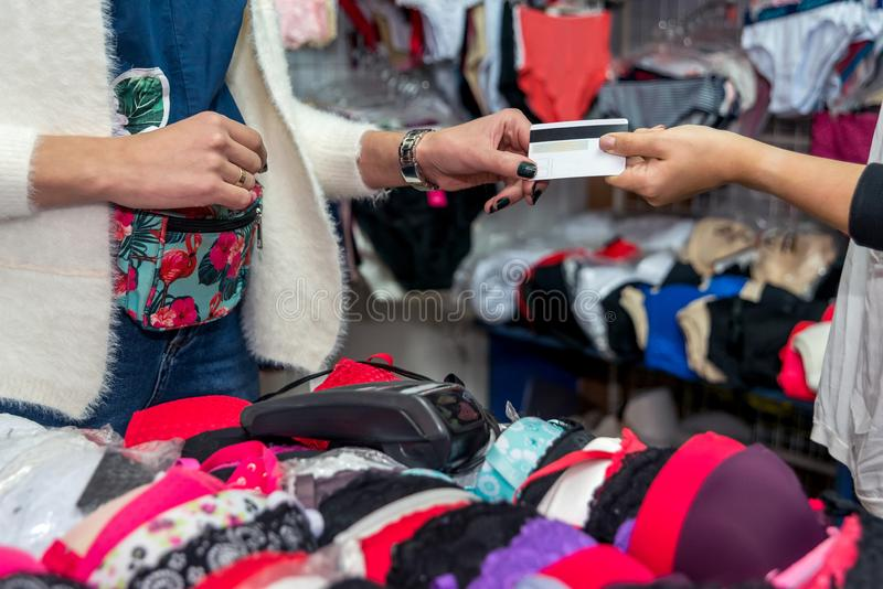 Klienten som ger kreditkorten för betalning i underkläder, shoppar arkivfoto