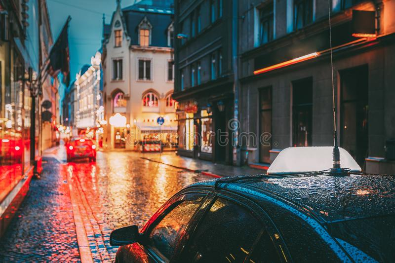 Klienter för taxibilväntan i gamla europeiska gator i regnig afton royaltyfria foton