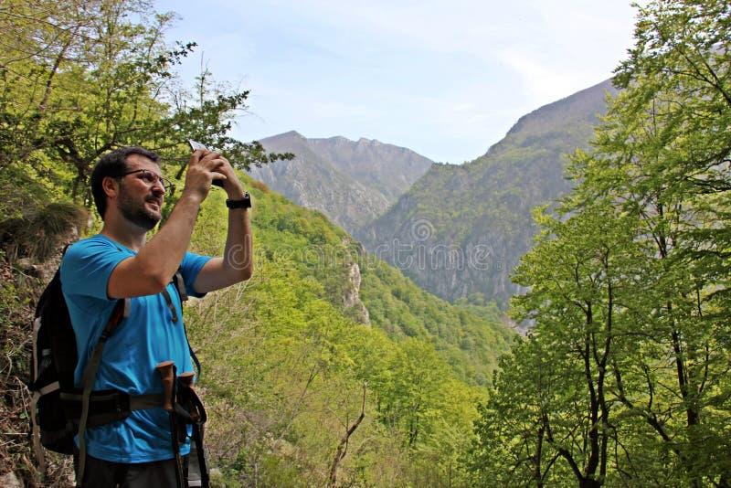 Klimmer in de bergen die foto's nemen stock fotografie