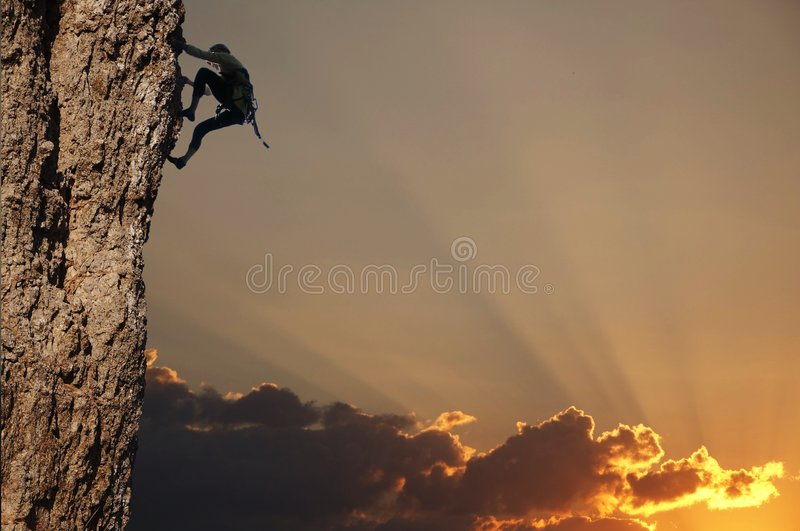 Klimmer op zonsondergang op de rots