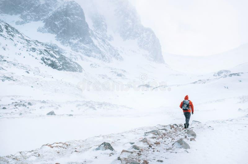 Klimmergangen alleen in hooggebergte bij winderig sneeuwweer stock afbeeldingen