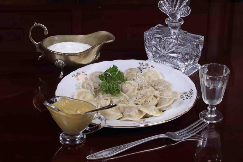 Klimpar tjänade som med gräddfil, senap och vodka royaltyfri bild