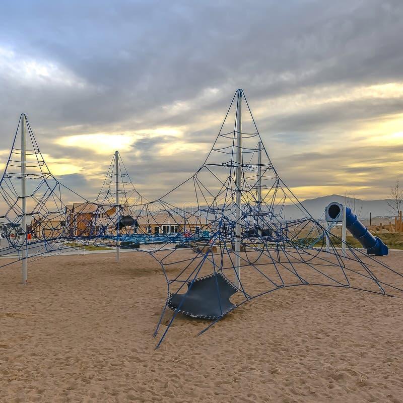 Klimrek en tunnels van de kader de het Vierkante Kabel bij een speelplaats onder bewolkte hemel bij zonsondergang stock foto