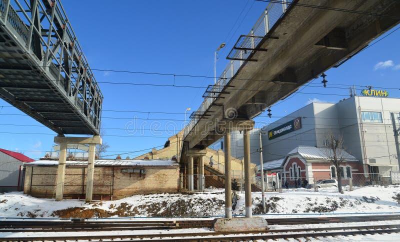 Klin, Rússia - 27 de fevereiro 2016 Ponte pedestre sobre as trilhas de estrada de ferro na estação imagem de stock