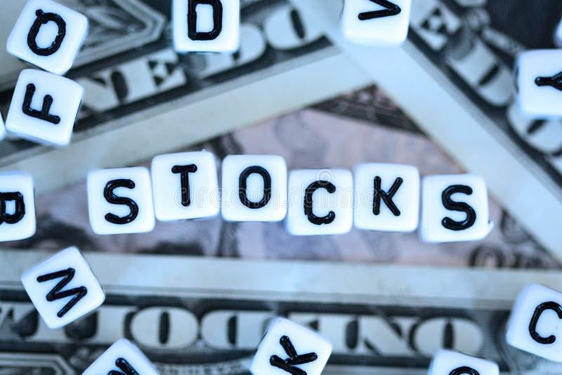 """Klingerytów listowi sześciany literuje """"stocks† na my dolarów rachunków tło zdjęcie royalty free"""