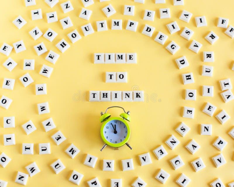 Klingerytu blokowy sześcian z słowem czas MYŚLEĆ i wokoło rozrzuconych indywidualnych listów i budzika na żółtym tle fotografia stock