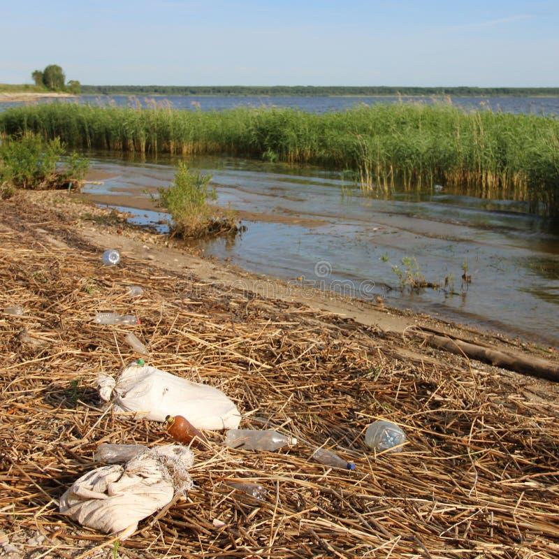 Klingerytu butelki, torby i śmieci, kłamają na brzeg odpady, brud, zanieczyszczenie środowiska zdjęcia stock