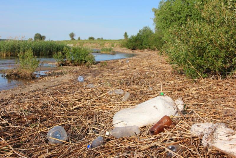 Klingerytu butelki, torby i śmieci, kłamają na brzeg odpady, brud, zanieczyszczenie środowiska zdjęcie stock