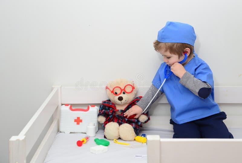 klinik Entz?ckendes Kind gekleidet als Doktor, der mit Spielzeug spielt Gesundheitsprüfung durch junge medizinische Arbeitskraft  stockfotografie