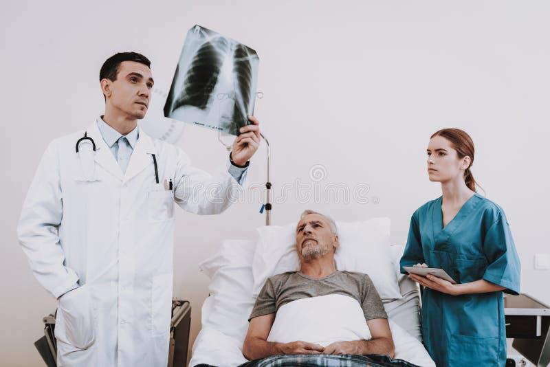 Klinik och doktor med patienten Man i sjukhus arkivbilder