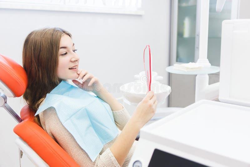 klinika stomatologicznej Przyjęcie, egzamin pacjent Ząb opieka Młoda dziewczyna ono uśmiecha się, patrzejący w lustrze po a zdjęcie stock