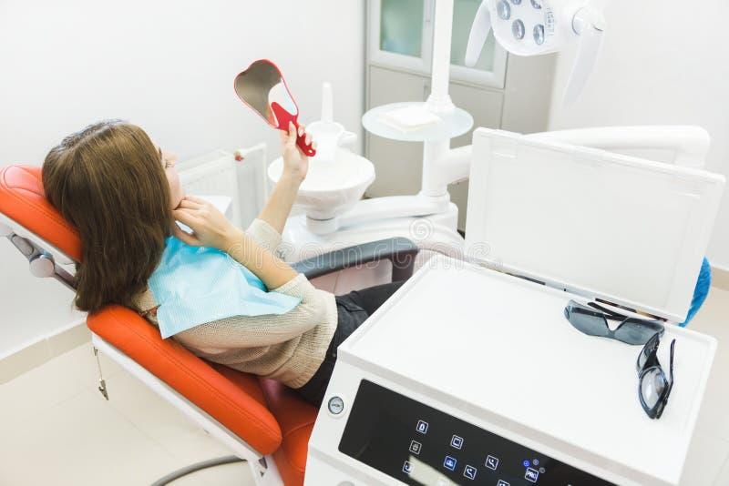klinika stomatologicznej Przyj?cie, egzamin pacjent Z?b opieka M?oda dziewczyna ono u?miecha si?, patrzej?cy w lustrze po a obrazy stock