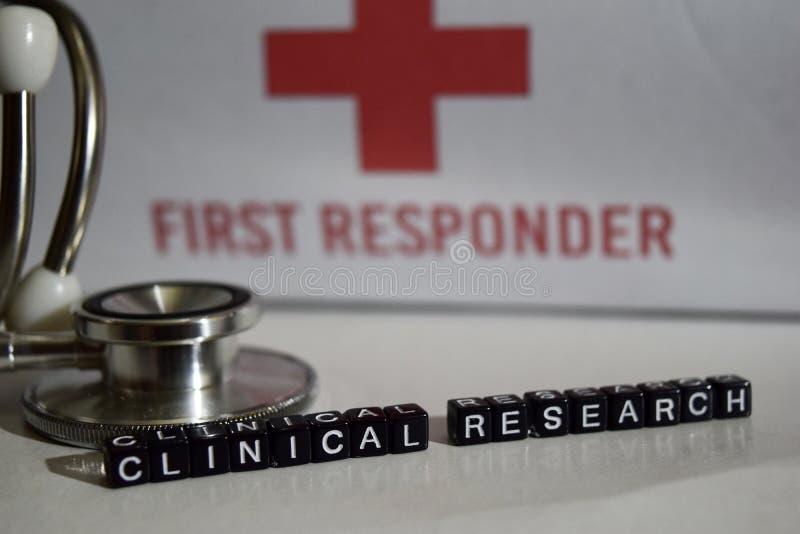 Klinische Forschungsmitteilung geschrieben auf Holzklötze Stethoskop, Gesundheitswesenkonzept stockfotos