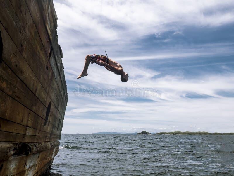Klip die springen: Een jonge kerel in borrels springt in zeewater van de kant van een oud schip stock foto's