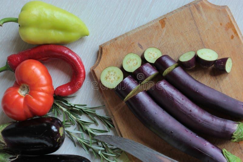 Klipp auberginecirklarna på plankan, peppar, och tomater är på tabellen royaltyfri fotografi