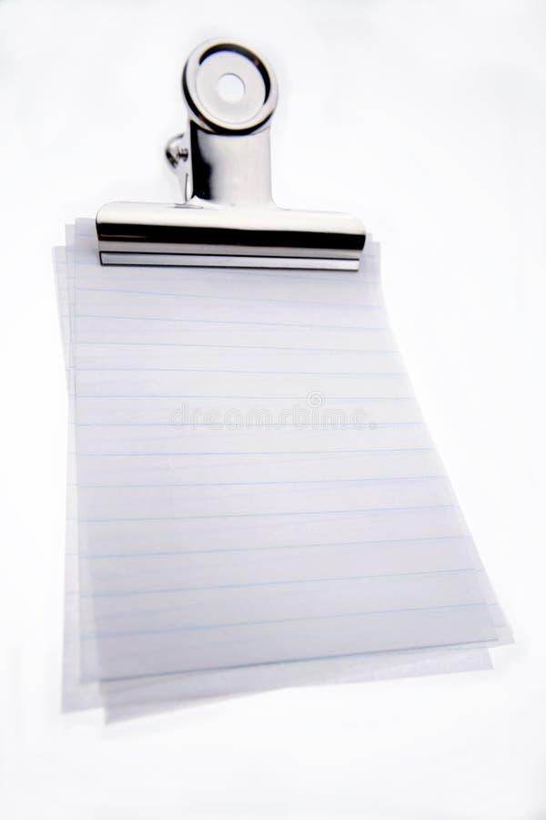 Klipp auf unbelegten gezeichneten Papieren stockfotografie