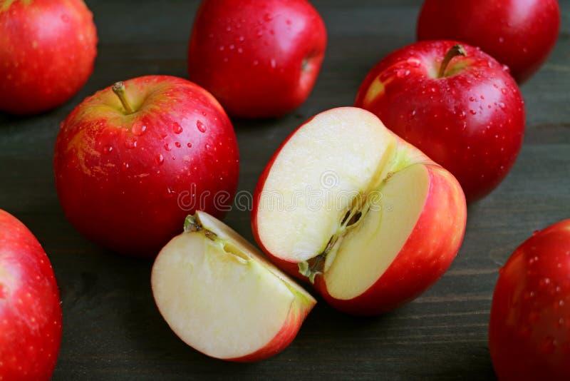 Klipp det nya mogna röda äpplet bland många hela frukter med vattensmå droppar spridda på den mörka bruna trätabellen royaltyfri fotografi