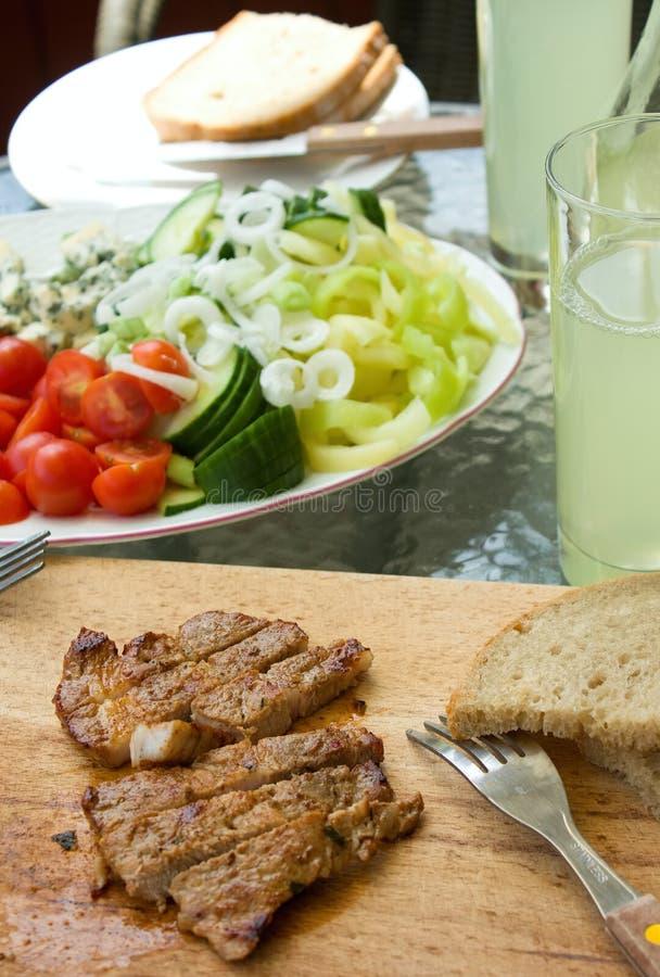 Klipp grisköttbiff med grönsaken på det trädgårds- partiet royaltyfri foto
