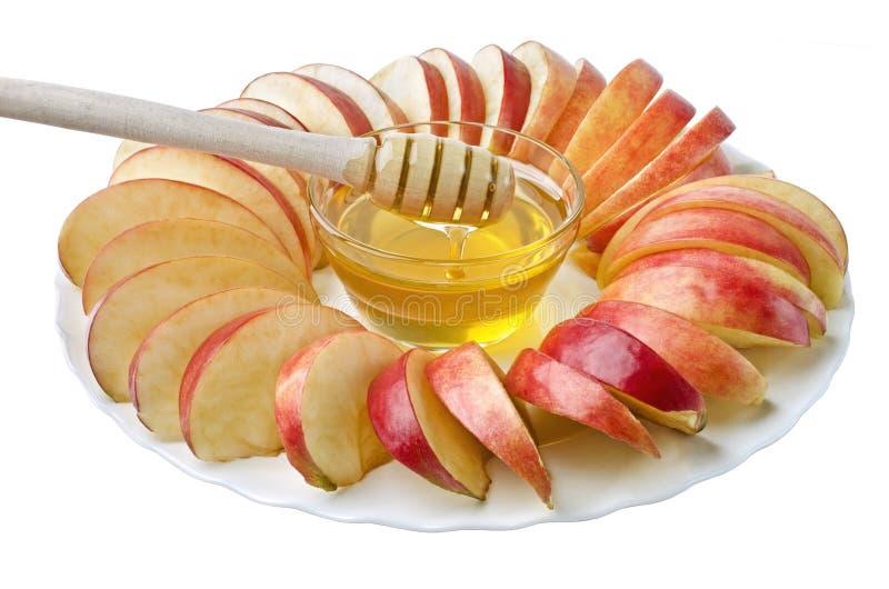 Klipp in i skivor av äpplen med en bunke av honung royaltyfria bilder