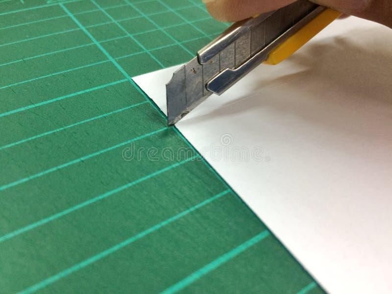 Klipp papper med en kniv fotografering för bildbyråer