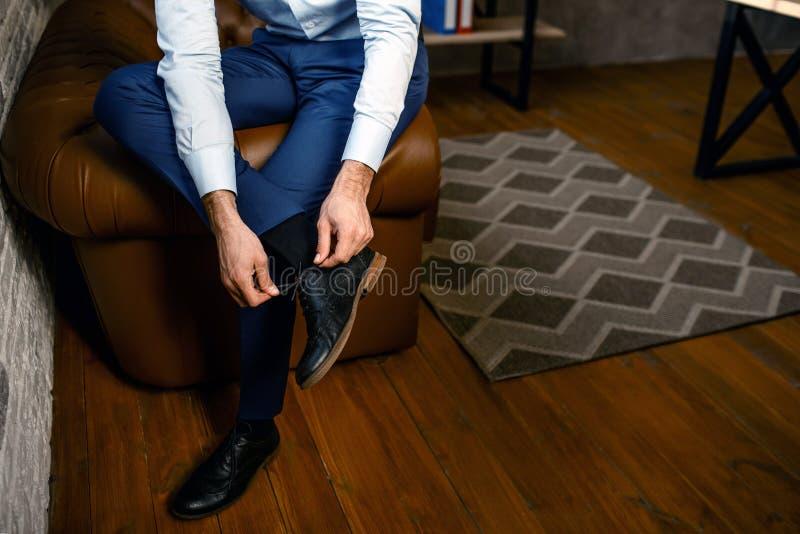 Klipp sikten av den unga stiliga affärsmannen i hans eget kontor Han rymmer benet på ett annat, och bandet snör åt på skor upptag royaltyfri foto