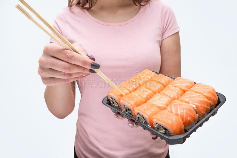 Klipp sikten av hållplattan för den unga kvinnan med sushi Hon trycker på dem med pinnar bakgrund isolerad white royaltyfri foto