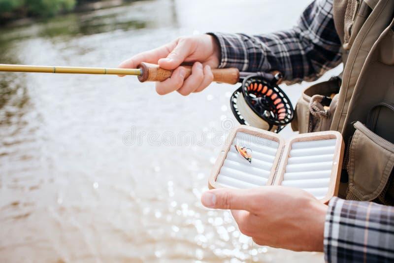 Klipp sikten av mananseendet i vatten- och innehavsnurr med rullen i en hand och en ask med ett konstgjort silikon royaltyfri bild