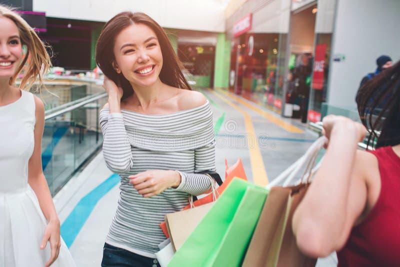 Klipp sikten av positiva och lyckliga flickor som tillsammans går Den asiatiska flickan rymmer hennes hår och le Hennes blondy vä royaltyfria bilder
